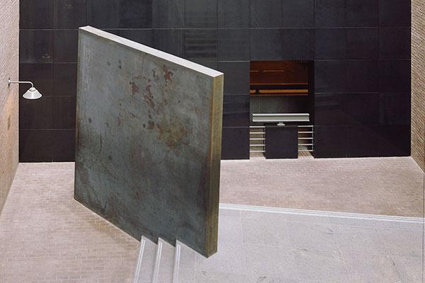 <p>Richard Serra's monolithic sculpture <em>Gravity</em> is wedged near the black granite wall at the bottom of the stairs in the southwest corner of the Hall of Witness.</p>