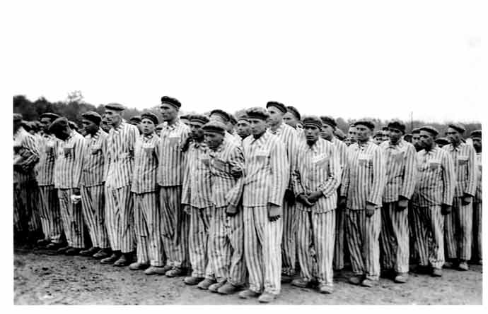 Prisoners standing for roll call at the Buchenwald concentration camp in Germany, circa 1938. This twice-daily ordeal of several hours in all weather was so the SS guards could account for every single prisoner. Roll calls of many hours' duration were used also as camp-wide punishment, often ending in death for the weakest. The prisoners' uniforms bear classifying triangular badges and identification numbers. Homosexual prisoners were identified by pink triangle badges.