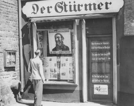 "A young man looks at the antisemitic caricature in the display window of the Danzig office of ""Der Stuermer."" The poster reads: ""The Jews are our misfortune."" Danzig, 1939."