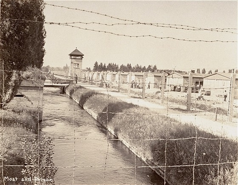View of a section of the newly liberated Dachau concentration camp as seen through the barbed-wire fence. Dachau, Germany, May 1945.