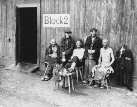 Five Jewish survivors pose for a US Signal Corps photographer in front of Block 2 in the Hanover-Ahlem camp, a subcamp of Neuengamme. Hanover-Ahlem, Germany, April 11, 1945.