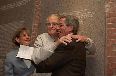 Liberator Vernon Tott of the 84th Infantry was honored by some of the survivors he helped free from the Ahlem labor camp near Hanover, Germany. Tott's name was engraved on the Museum's Donor's Lounge wall with the inscription: In honor of Vernon W. Tott, my liberator & hero. The ceremony in which Tott's name was unveiled came as a complete surprise to him. This photograph shows Sara J. Bloomfield (Director, United States Holocaust Memorial Museum), Vernon Tott, and Fred S. Zeidman (Chair, United States Holocaust Memorial Council) after the ceremony honoring Tott. Washington, DC, November 2003.