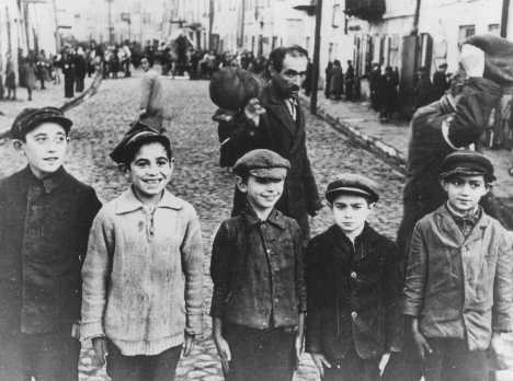 Jewish children in the Lublin ghetto. The men behind them were forced to remove their caps in deference to a German officer standing next to the photographer. Poland, 1941–1942.