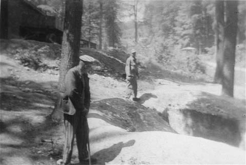 Two survivors at one of the human-ash pits in the Dora-Mittelbau concentration camp, located near Nordhausen. Germany, April-May 1945.