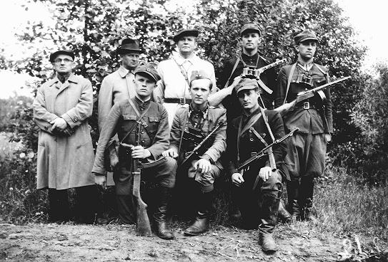 "Pro-Soviet partisans, part of the Polish People's Army (AL), during a visit from General ""Rola"" Zymierski (standing, third from left) in German-occupied Poland. Parczew Forest (around Lublin), Poland, 1944."