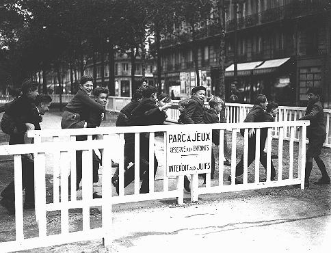 In German-occupied Paris, the fence around a children's public playground bears a sign forbidding entrance to Jews. Paris, France, November 1942.