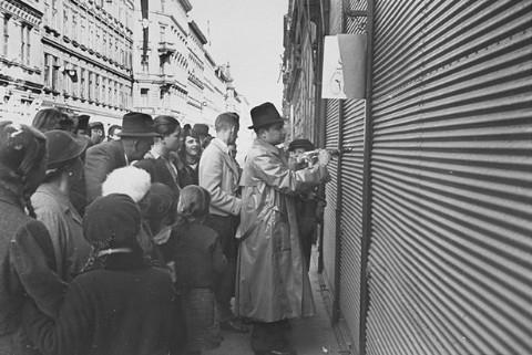 A Jewish man forced to paint anti-Jewish graffiti on a shuttered storefront. Vienna, Austria, March 1938.