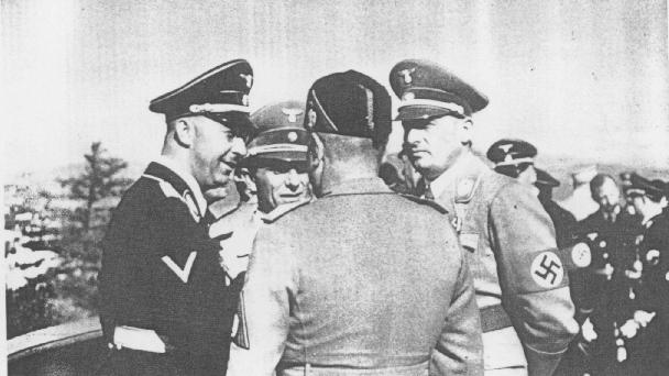 Durante una visita in Germania, il dittatore italiano Benito Mussolini (di spalle) parla con (da sinistra a destra) il comandante delle SS Heinrich Himmler, il ministro della propaganda Joseph Goebbels, e il governatore nazista della Polonia, Hans Frank. Germania 1941.