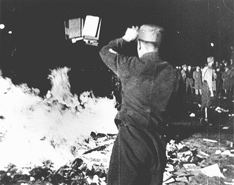 "At Berlin's Opernplatz, an SA man throws books into the flames at the public burning of books deemed ""un-German."" Berlin, Germany, May 10, 1933."