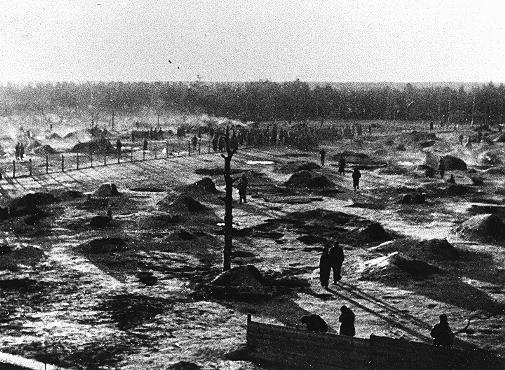 View of a camp for Soviet prisoners of war, showing the holes dug into the ground that served as shelter. The camp was located south of Hamburg in northern Germany. Wietzendorf, Germany, 1941–1942.
