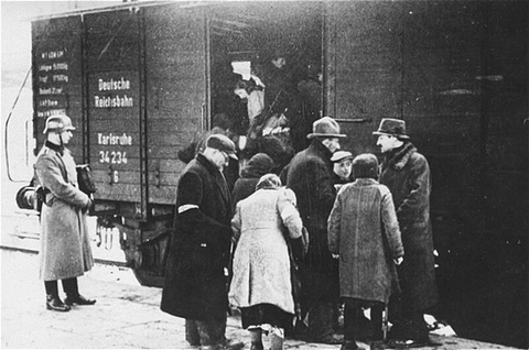 A member of the German SS supervises the boarding of Jews onto trains during a deportation action in the Krakow ghetto. Krakow, Poland, 1941–1942.