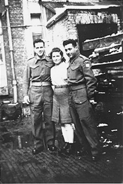 "A Jewish Brigade soldier with two members of ""Kibbutz Buchenwald,"" a group of survivors from the Buchenwald concentration camp preparing for agricultural work in Palestine. Antwerp, Belgium, 1946."