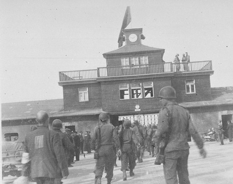 American soldiers and liberated prisoners at the main entrance of the Buchenwald concentration camp. Germany, May 1945.