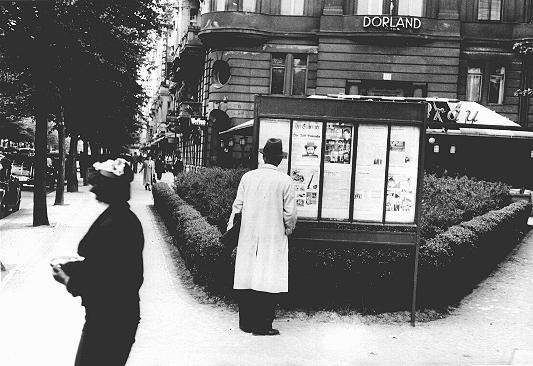 "A pedestrian stops to read an issue of the antisemitic newspaper ""Der Stuermer"" (The Attacker) in a Berlin display box. ""Der Stuermer"" was advertised in showcase displays near places such as bus stops, busy streets, parks, and factory canteens throughout Germany. Berlin, Germany, probably 1930s."