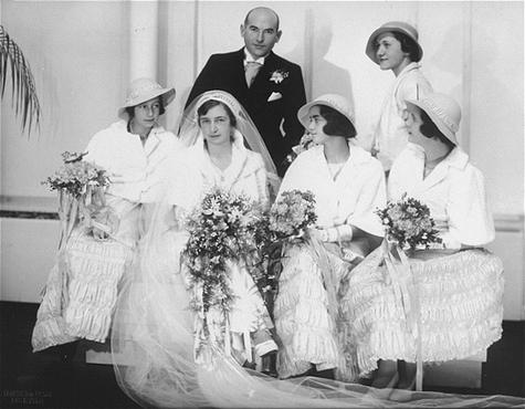 Retrato de Hilde e Gerrit Verdoner no dia de seu casamento juntos com suas quatro damas-de-honra.  Elas  eram: Jetty Fontijn (primeira à esquerda), Letty Stibbe (segunda a partir da direita), Miepje Slulizer (primeira à direita), e Fanny Schoenfeld (em pé, atrás).  Bélgica, entre 1933 e 1937.