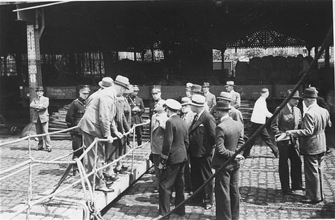 "Belgian officials at the gangplank of the ""St. Louis"" after the ship was forced to return to Europe from Cuba. Belgium granted entry to some of the passengers. Antwerp, Belgium, June 1939."