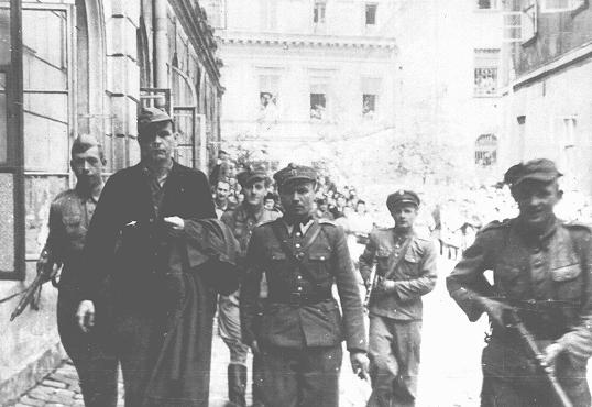 Amon Goeth (front left), commandant of the Plaszow camp, under escort to the courthouse in Krakow for sentencing. He was sentenced to death at his postwar trial on war crimes charges. Krakow, Poland, August 1946.