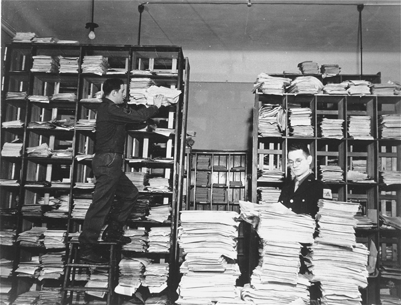 US Army staffers organizing stacks of German documents collected by war crimes investigators as evidence for the International Military Tribunal.