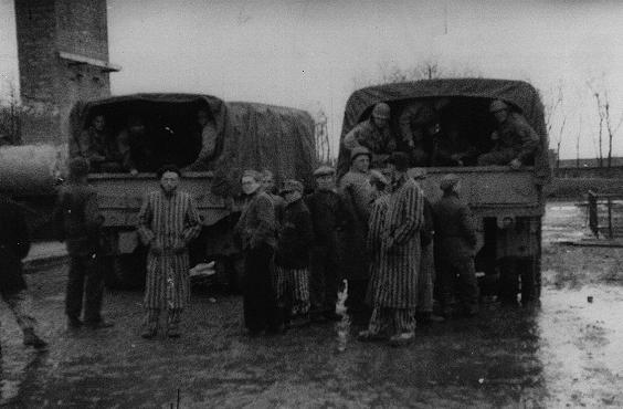 Foto de alguns sobreviventes do campo de concentração de Buchenwald parados atrás de dois caminhões que transportavam tropas norte-americanas. Alemanha, maio de 1945.