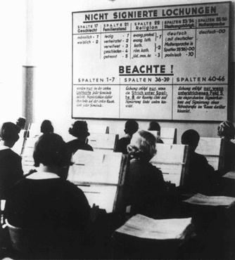 German women at work in the offices of the German Census Bureau. The board gives directions for tabulation: the center column instructs that number 3 is the indicator to be used for Jews. Germany, 1933.