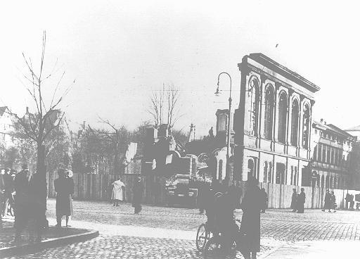 """Единственная уцелевшая стена синагоги Бёрнплац, разрушенной во время погрома """"Хрустальной ночи"""" (""""Ночи разбитых витрин""""). Прохожие наблюдают за уборкой развалов и вывозом обломков синагоги. Франкфурт-на-Майне, Германия, январь 1939 года."""