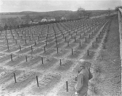 A US Army soldier views the cemetery at the Hadamar Institute, where victims of the Nazi euthanasia program were buried in mass graves. This photograph was taken by an American military photographer soon after the liberation. Germany, April 5, 1945.