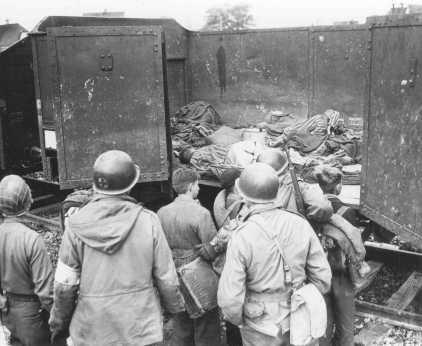 Soldados norte-americanos encontraram do lado de fora do campo de Dachau estes vagões carregados de corpos.  Para que fossem testemunhos do horror cometido pelo seu povo, os soldados fizeram com que jovens alemães—possivelmente membros da Juventude Hitlerista (HJ)—- vissem a atrocidade de perto. Dachau, Alemanha, 30 de abril de 1945.