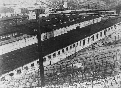 Vista, através do arame farpado, dos barracões de prisioneiros no campo de concentração de Flossenbürg. Flossenbürg, Alemanha, 1942. [Imagem: Bildarchiv Preussischer Kulturbesitz]