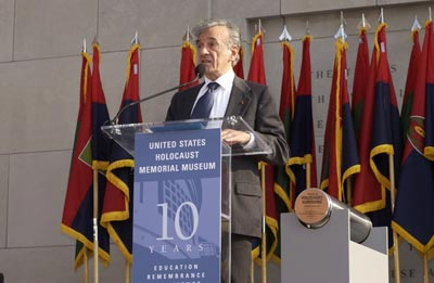 Elie Wiesel became Founding Chairman of the United States Holocaust Memorial Council in 1980. Here, he speaks at a ceremony held during the Tribute to Holocaust Survivors, one of the Museum's tenth anniversary events. Flags of US Army liberating divisions form the backdrop to the ceremony. Washington, DC, November 2003.