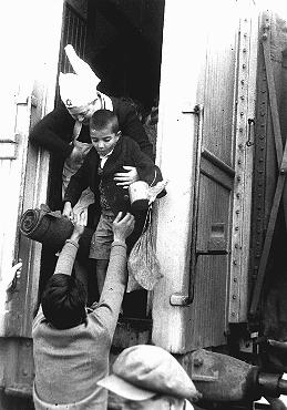"A nurse helps one of the ""Tehran Children,"" Polish Jewish refugees, disembark from a train at the Atlit absorption center. Atlit, Palestine, February 18, 1943."