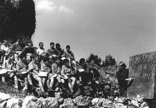 "Some of the ""Tehran Children,"" Polish Jewish refugees, study Hebrew in a Jewish National Fund youth village near Jerusalem. Palestine, March 9, 1943."
