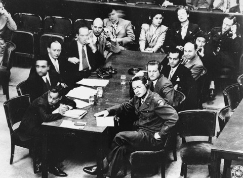 US Brigadier General Telford Taylor (front right), chief of counsel, sits at the prosecution table with his staff during the reading of charges against the defendants in the RuSHA Trial. October 10, 1947.