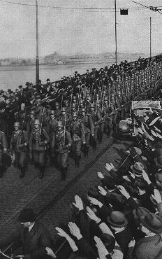 During the remilitarization of the Rhineland, German civilians salute German forces crossing the Rhine River in open violation of the Treaty of Versailles. Mainz, Germany, March 7, 1936.