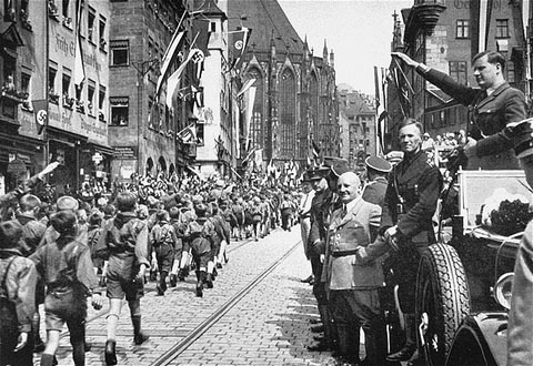 Members of the Hitler Youth march before their leader, Baldur von Schirach (at right, saluting), and other Nazi officials including Julius Streicher. Nuremberg, Germany, 1933.