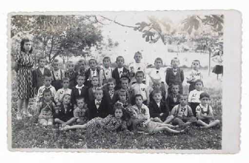 Gavra Mandil and his family narrowly escaped death in German-held Yugoslava by fleeing to Italian-occupied Albania. There Gavra attended a school in Kavaja that had both Muslim and Christian pupils. He is seated on the far right in the first row. June 1943.