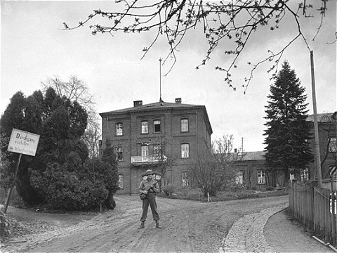 An American soldier stands guard in front of the Hadamar Institute. The photograph was taken by an American military photographer soon after the liberation. Germany, April 5, 1945.