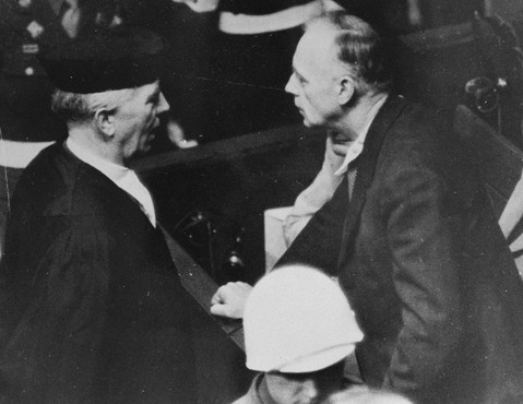 Joachim von Ribbentrop (Foreign Minister of Germany from 1938 to 1945) speaks with his lawyer, Dr. Fritz Sauter, in the Nuremberg courtroom.