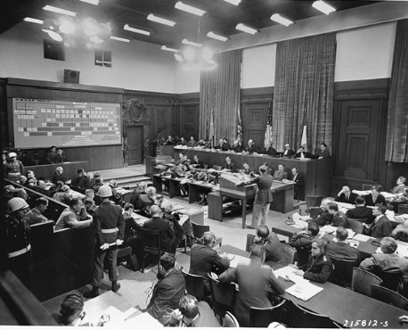 American Major Frank B. Wallis (standing center), a member of the trial legal staff, presents the prosecution's case to the International Military Tribunal at Nuremberg. A chart (top left) shows where the defendants (bottom left) fit into the organizational scheme of the Nazi party. At right are lawyers for the four prosecuting countries. November 22, 1945.