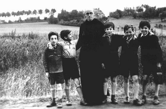 """Padre Bruno insieme ad alcuni bambini ebrei che egli aveva nascosto ai Tedeschi. Yad Vashem riconobbe Padre Bruno """"Giusto fra le Nazioni"""". Belgio, tempo di guerra."""