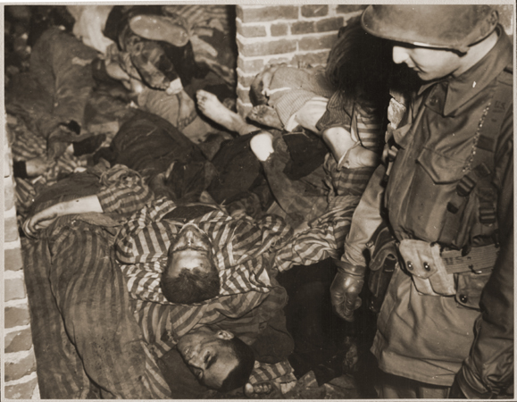 An American soldier views the bodies of prisoners piled on top of one another in the doorway of a barracks in Wöbbelin. Germany, May 4-5, 1945.
