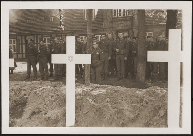 After the liberation of the camp, the US Army ordered the local townspeople to bury the corpses of prisoners killed in the camp. This photograph shows troops observing a moment of silence at a mass funeral for victims of the Wöbbelin camp.  Germany, May 7, 1945.
