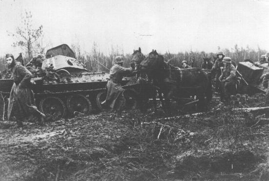 A German army column struggles through the mud, past a destroyed Soviet tank.  Nevel, Soviet Union, fall 1943.