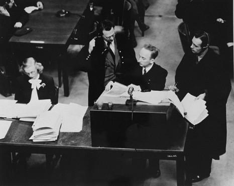 El Procurador General de Justicia Benjamin Ferencz presenta las pruebas durante el juicio a los Einsatzgruppen (equipos móviles de matanza). Ferencz está rodeado por los abogados defensores alemanes, el Dr. Friedrich Bergold (a la derecha, abogado de Ernst Biberstein) y el Dr. Rudolf Aschenauer (a la izquierda, abogado de Otto Ohlendorf), que objetan la presentación de ciertos documentos como pruebas.