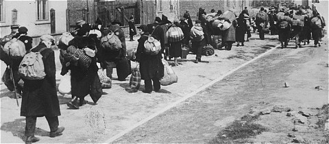 Jews carrying their possessions during deportation to the Chelmno killing center. Most of the people seen here had previously been deported to Lodz from central Europe. Lodz, Poland, between January and April 1942.