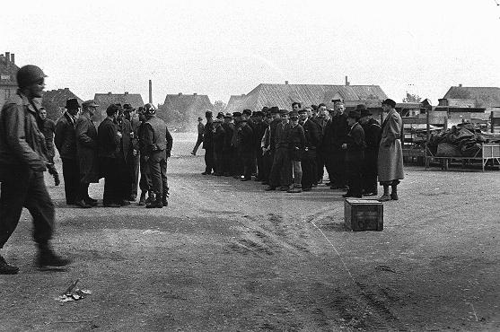 German civilians are assembled by American officials before being detailed to collect and bury victims of the Buchenwald subcamp at Langenstein-Zwieberge. Germany, April 1945.