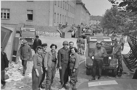 American medical personnel in front of a school that has been converted into a hospital for concentration camp survivors from Langenstein. Germany, April 1945.