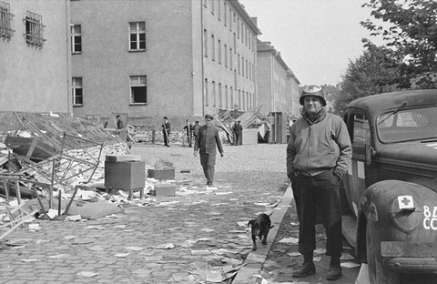 An American medical officer stands in front of a school that has been converted into a hospital for concentration camp survivors from Langenstein-Zwieberge. Germany, April 1945.