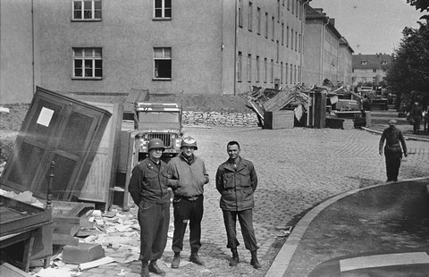 American medical personnel stand in front of a school that has been converted into a hospital for concentration camp survivors from Langenstein-Zwieberge. Germany, April 1945.