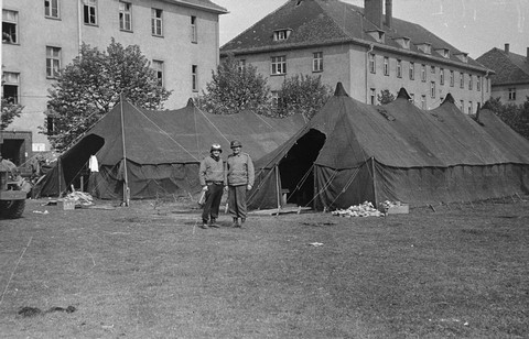 American medical personnel in front of two tents set up outside a school converted into a hospital for concentration camp survivors from Langenstein. Germany, April 1945.