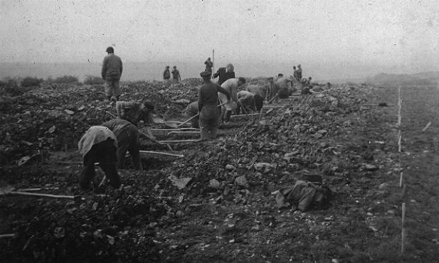 German civilians conscripted from nearby towns dig graves for some of the victims of the Ohrdruf camp. Ohrdruf, Germany, April 1945.